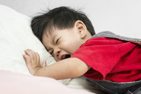 Asia Baby Crying on the bed Put on a red shirt.