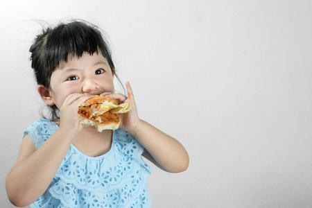 블루 타이 복장 소녀 햄버거를 먹는 의도 재미와 소녀.