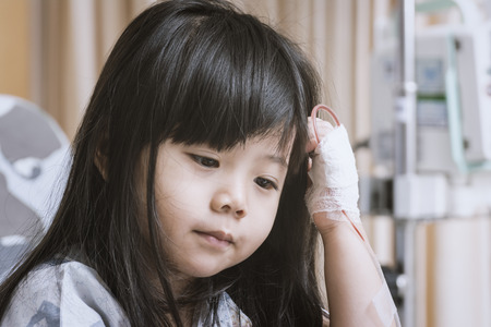Little Cute Girl in the Hospital Sit on the patient bed  to wait for treatment. Stock Photo - 84650131