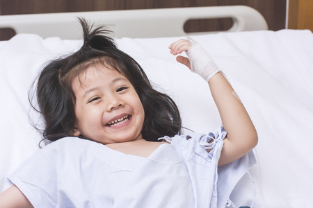 Cute Patient Little Asian Girl Smile on Bed in hospital.