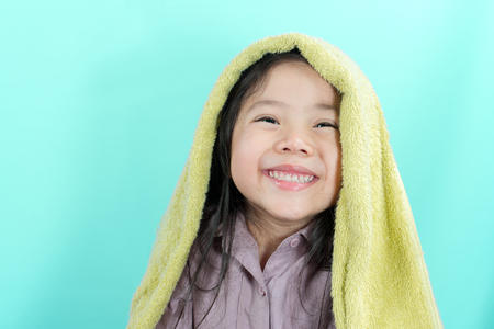 Cute little Asian girl smiled cheerfully while preparing to bathe on the bright green background.