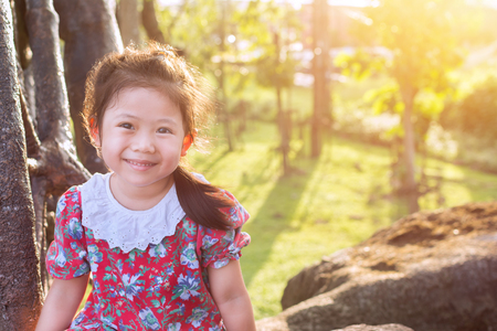 Cute Little Girl in red dress with flower pattern Smiling cheerfully on the stones in the garden in the evening and a fresh atmosphere.
