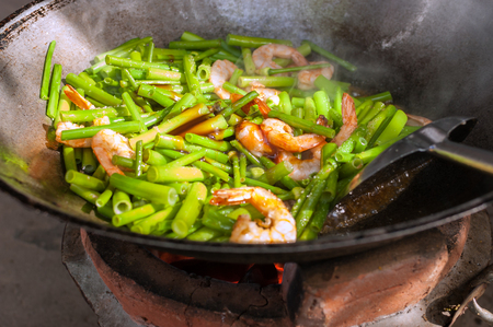 Stir-Fried Onion Flowers with shrimp In a Pan on a Charcoal Stove. Foto de archivo