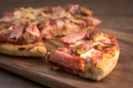Hot Pizza Ham and Bacon Break into pieces on Cutting Board Breakfast in the Morning with Sun Light on Wooden Table. Foto de archivo