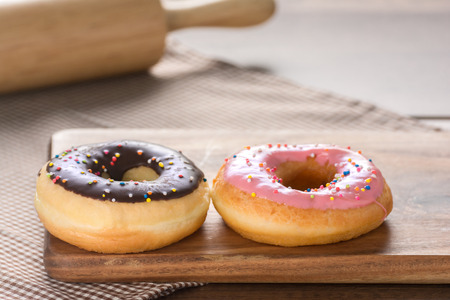 A Homemade donuts at the weekend, which are ready to Eat in the Morning, include chocolate and strawberries. Placed on a wooden chopping board And brown tablecloth