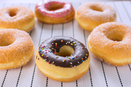 A Homemade donuts at the weekend, which are ready to Eat in the Morning, include chocolate and strawberries. Placed on a wooden chopping board And White tablecloth. Foto de archivo