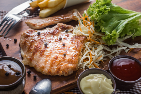 Pork Chop Steak Recipe with Vegetables, French Fries, Salad Sauce, and Ketchup. Prepared on Wooden Table. Foto de archivo