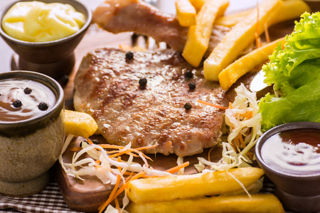 Pork Chop Steak Recipe with Vegetables Put together French Fries, Salad Sauce, and Ketchup. Prepared on Wooden Table. Foto de archivo