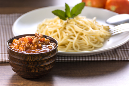 Spaghetti with Pork Tomato Sauce in Wooden Cup And spaghetti on Wooden Table.