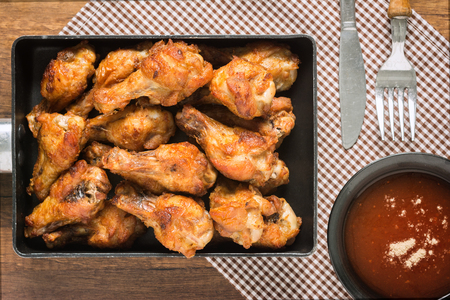 Grilled chicken Wings on a Saucepan and chili sauce topped with pepper is an appetizer for kids and adults in the summer. Made simple in the kitchen.