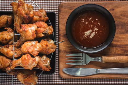 Grilled chicken Wings on a Saucepan and chili sauce topped with pepper on a cutting board, is an appetizer for kids and adults in the summer. Made simple in the kitchen.