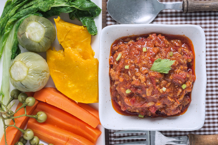Northern Thai Meat and Tomato Spicy Dip in White Cup on Wooden Table with Vegetables Concept of Thai food.