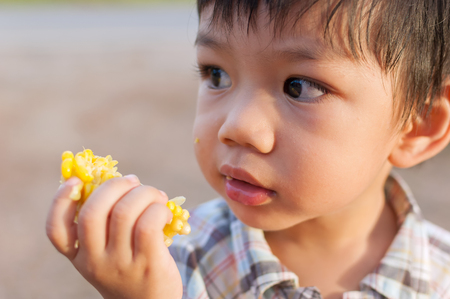 A Little  Asian boy eats corn in his hand. Delicious cheerfully. And wonder what this is. And is a complete healthy child. Foto de archivo