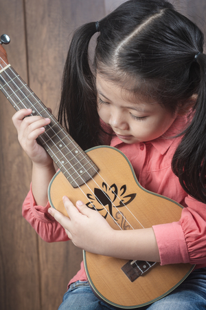 Portrait of cute Little girl looking and playing Ukulele With the intention of practicing. of musical instruments. on wooden background, funny concept. Foto de archivo