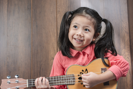 Portrait of cute Little girl playing Ukulele of musical instruments. on wooden background, funny concept. with space for text.