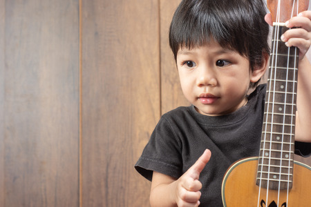 Portrait of cute Little Boy playing Ukulele of musical instruments. on wooden background, funny concept. with space for text.