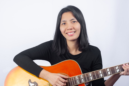 Portrait of Beautiful Asian Women playing Guitars With the intention of practicing. of musical instruments. on Isolate White background, music concept. Foto de archivo