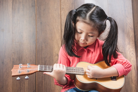 Portrait of cute Little girl looking and playing Ukulele With the intention of practicing. of musical instruments. on wooden background, funny concept. with space for text.