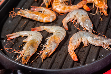 Close up Cooking Seafood Shrimp in the Evening at the Beach. Taken by the light of the sun.