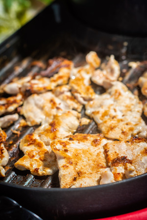 Grilled pork is cooked on a black electric grill. Eat foods for everyone in the family.