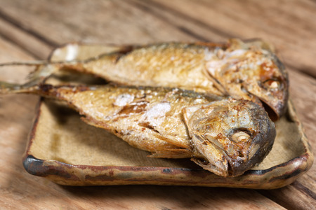 Close up  Fried mackerels on old yellow plate. Thai Recipe with Space for text. Foto de archivo