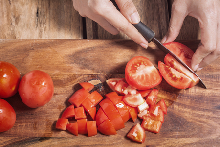 Cut tomatoes to cook healthy on a wooden cutting board. Using flash photography studio Foto de archivo