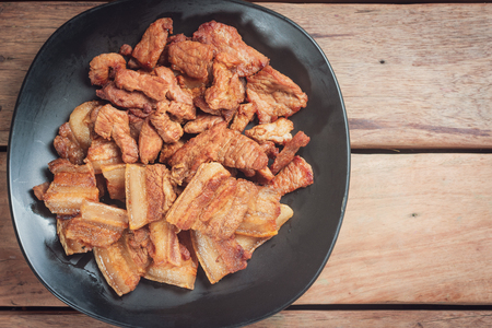 Pork fried on a Black plate while hot and ready to serve. To eat food in Asia. All food is eatable. with Space for Text. Foto de archivo