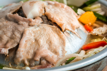 Grilled Pork in a round Pan with a variety of broth, such as Carrots, white Cabbage, Mushrooms, pumpkin Ingredients in food. Foto de archivo