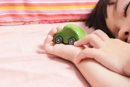 Close up Cute Little Asian boy lying on a bed of green toy car. with Space for Text.