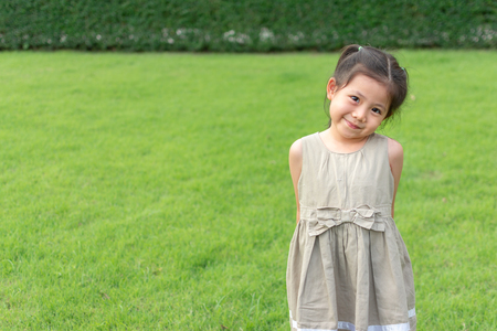 Cute Little Thai Girl Standing on green grass with embarrassed camera. with Space for Text.