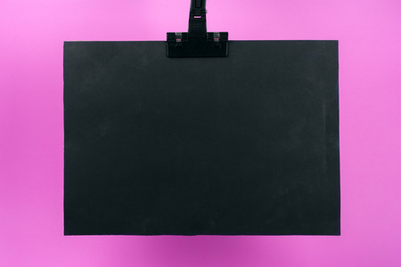 Blank black poster with binder clip mockup on pink background. copy space for text.