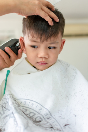 Cute Little Thai Boy Sit down peacefully for a haircut in stylish modernity. Foto de archivo