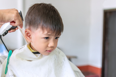 Cute Little Thai Boy Sit down peacefully for a haircut in stylish modernity. Foto de archivo