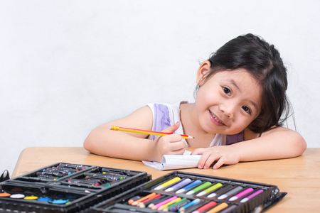 The girl with a pencil and a dress on the table in a lovely purple dress. Smile with the camera while drawing fun. with space for text. Foto de archivo