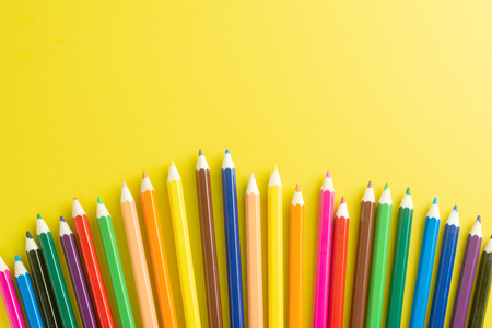 Close up Pencils Color on Yellow paper Arranged in a semicircle. with space for text. Back to School concept.