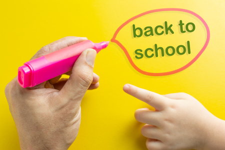 Pink Magic clolor in the hands of the father, which circle the word back to school. The daughter's hand is on the right. on yellow background concept.