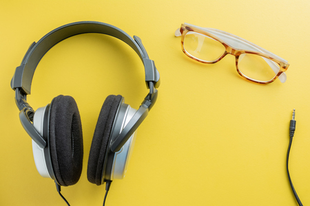Top view of Stereo Headphones and Spectacles Placed on the left of the image with space for text. the concept of relaxation from work.