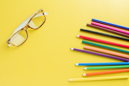Top view of Spectacles Placed on the left of the image and Pencils Color with space for text. creative design Concept.