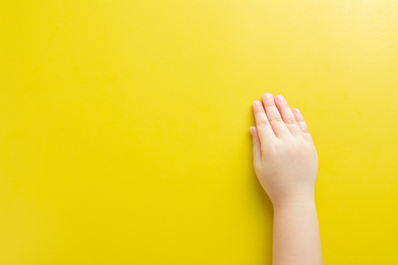 The hands are placed on the yellow paper background of the girl and leave space to enter the designs related to the child.