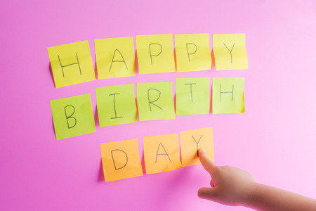 Handwriting happybirthday on post it.  And the child's hand pointing down to warn about important dates concept.