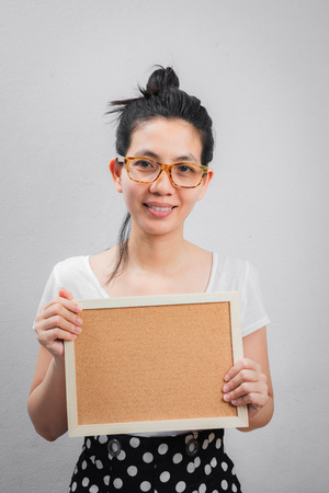 Asian Woman wearing glasses with white dress. Smile with happiness in comfortable days. wear the hair in a bun for Household work. and  holding blank card.