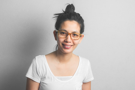 Asian Woman wearing glasses with white dress. Smile with happiness in comfortable days. wear the hair in a bun for Household work. Foto de archivo - 106505295