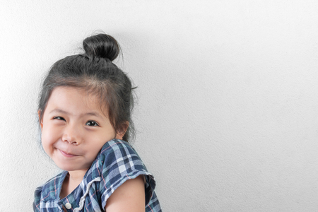 Portraits of Little Thai Girl wear the hair in a bun and plaid dress copy space for text. Foto de archivo