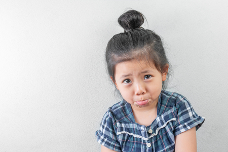 The Sadness of the Lovely Asian Girl wear the hair in a bun looking camera on White background with space for text.