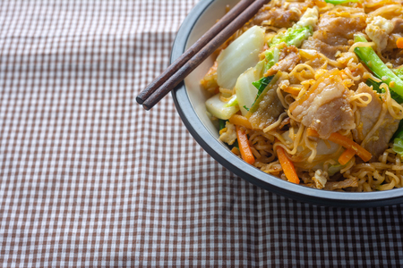 Fried instant noodles in Black Bowl. Cooked with a variety of pork and vegetables Recipe. The menu is easy to eat and useful to the body. with space for text.