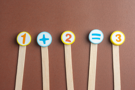 One Plus Tree Equals Four on Wooden Ice Cream Stick ,Using for Homeschooling Concept on Brown Background. Foto de archivo