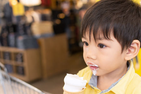 Close up Asian boy in yellow shirt Eat ice cream with delicious And look at the toy with interest. with space for text.