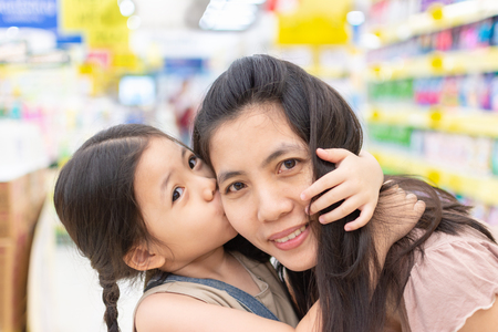 Close up Asian Mom and Daughter The cheek is happy because the mother Love Her and looking camera shot.