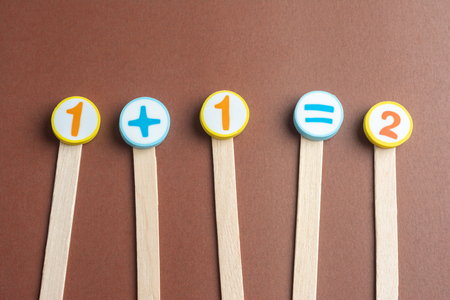 One Plus One Equals Two on Wooden Ice Cream Stick ,Using for Homeschooling Concept on Brown Background. Foto de archivo