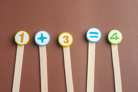 One Plus Three Equals Four on Wooden Ice Cream Stick ,Using for Homeschooling Concept on Brown Background. Foto de archivo